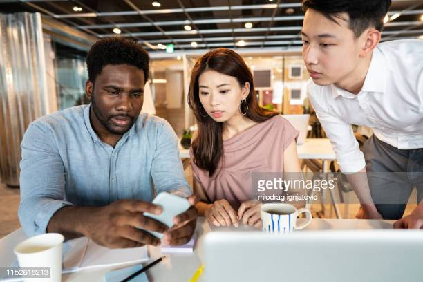 multi-ethnic group of coworkers sharing memes at work - meme stock pictures, royalty-free photos & images