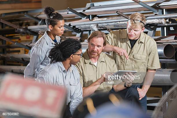 Multi-ethnic group of factory workers with supervisor