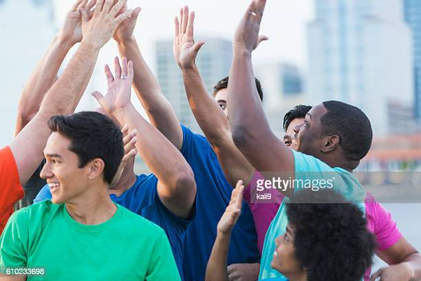 Multi-ethnic group of fathers and sons, high-five