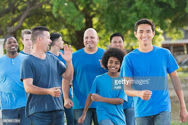 multi-ethnic group of fathers and sons walking together - marching stock pictures, royalty-free photos & images