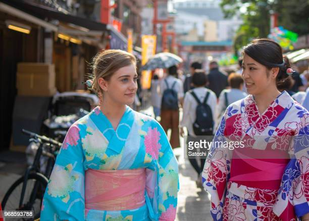 Multi-ethnic group of female friends in yukata walking in traditional Japanese town