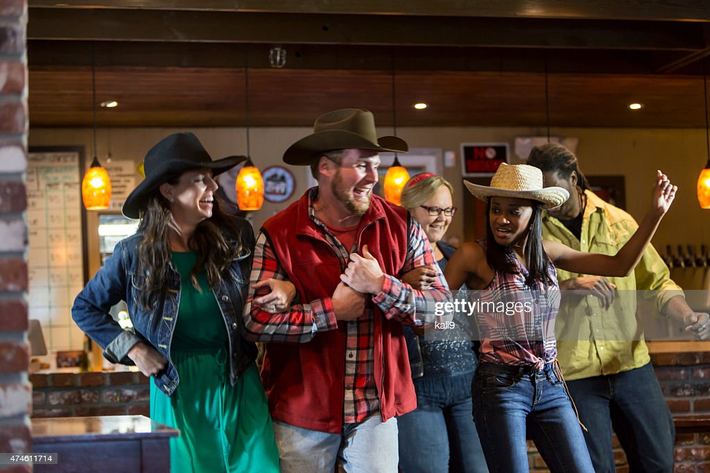 Multi-ethnic group of friends dancing in a bar : Stock Photo