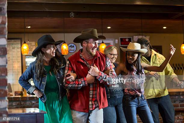 multi-ethnic group of friends dancing in a bar - cowboy hat stock pictures, royalty-free photos & images