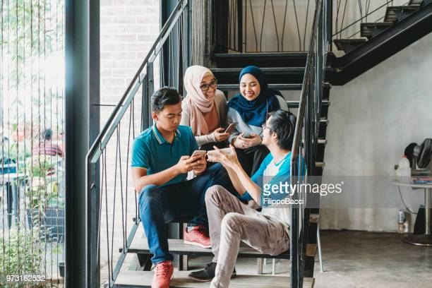 multiethnic group of friends using smart phones sitting on a staircase - malaysian culture stock pictures, royalty-free photos & images
