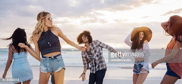 Multi-Ethnic Group of Hipster Friends Dancing on Sandy Beach