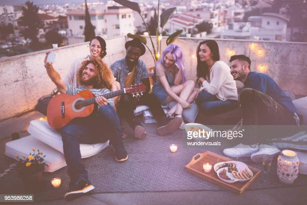 Multi-ethnic group of hipster friends taking selfies at rooftop party