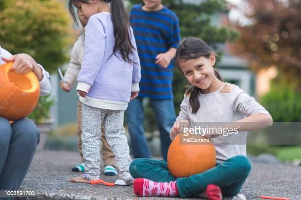 Multiethnic group of kids carving pumpkins