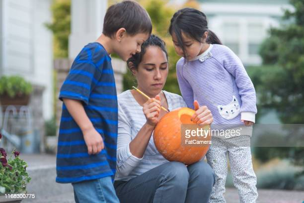 multiethnic group of kids carving pumpkins - carving craft product stock pictures, royalty-free photos & images