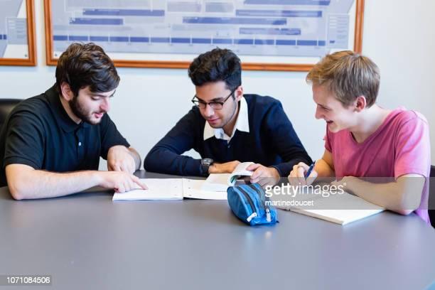 教室でのチームで作業する男性の大学生の多民族のグループ。