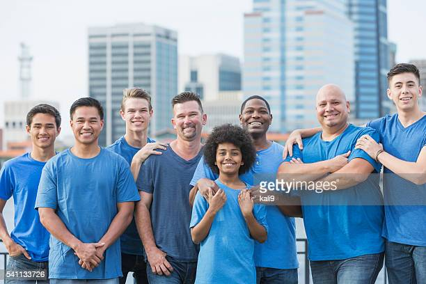 Multi-ethnic group of men and sons volunteering