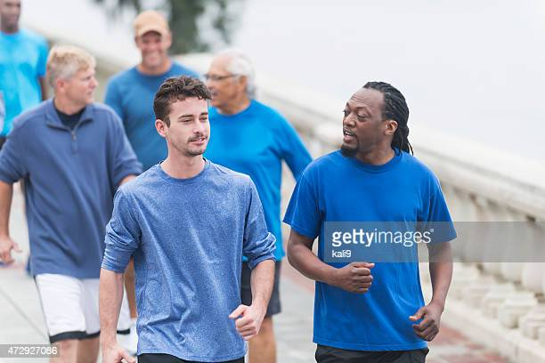 multi-ethnic group of men running in the park - charity benefit stock pictures, royalty-free photos & images