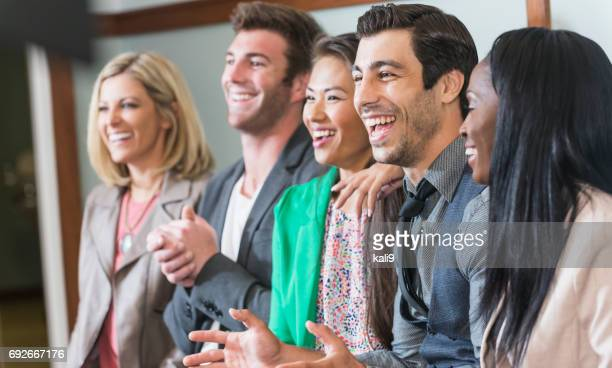 Multi-ethnic group of men, women watching presentation