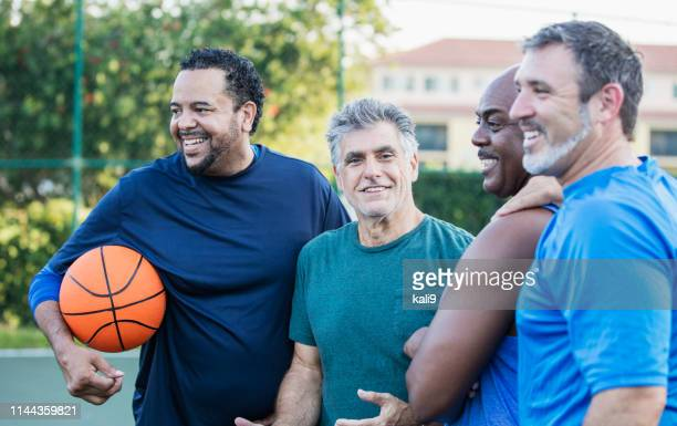 multi-ethnic group of middle aged men playing basketball - mature men stock pictures, royalty-free photos & images