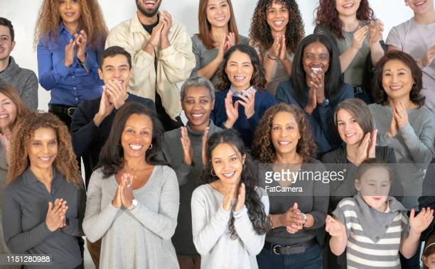 a multi-ethnic group of people clapping - black history month stock pictures, royalty-free photos & images