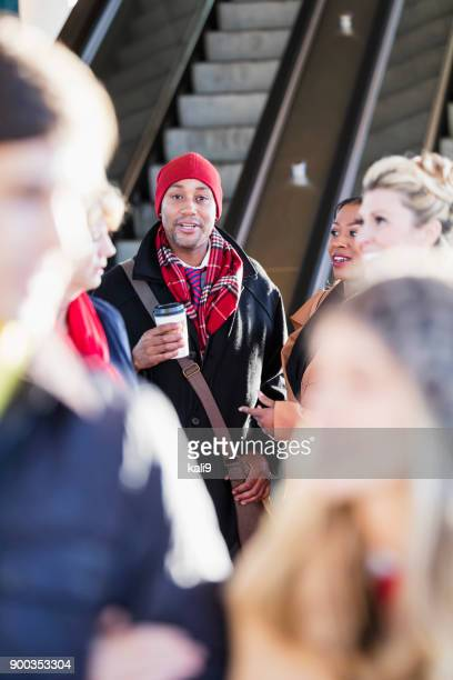 multi-ethnic group of people getting off escalator - stranger stock photos and pictures