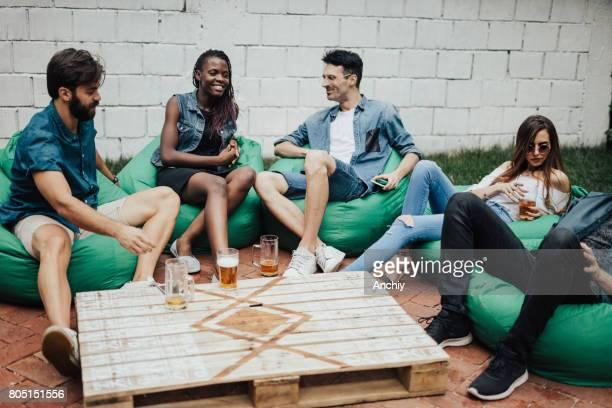 groupe multi-ethnique de personnes assises sur des poufs - sacco photos et images de collection