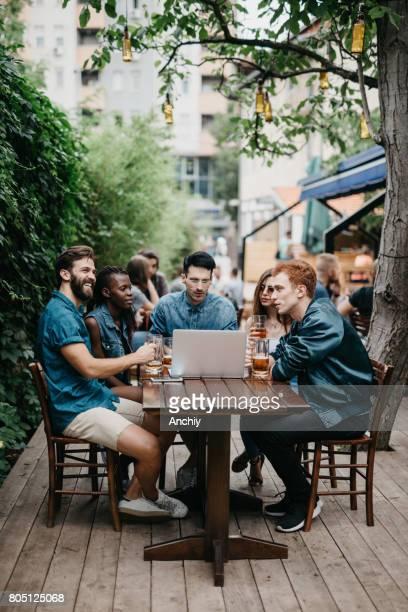 Multi-ethnischen Gruppe von Menschen, die mit Laptop in der Kneipe