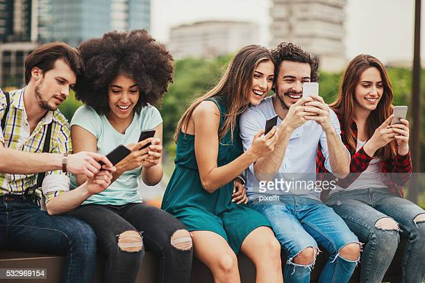Multi-ethnic group of people with phones outdoors