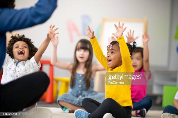 multi-ethnic group of preschool students in class - childhood stock pictures, royalty-free photos & images