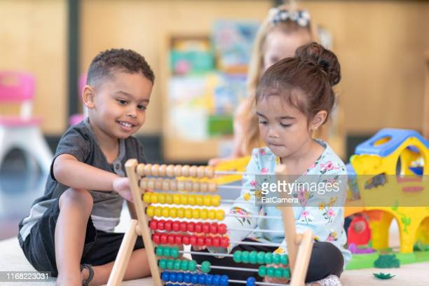 multi-ethnic group of preschool students playing together in classroom - montessori education stock pictures, royalty-free photos & images