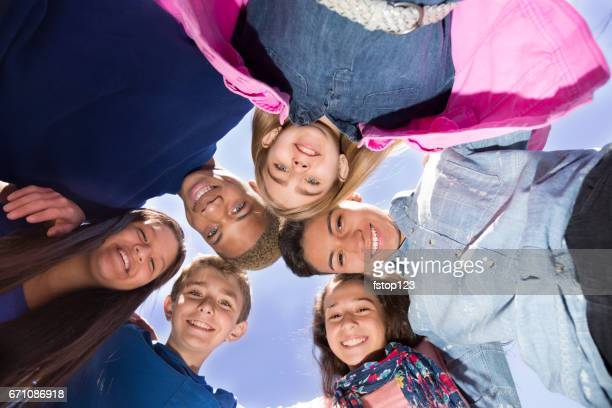 Multi-ethnic group of pre-teenagers hanging out in park with friends.