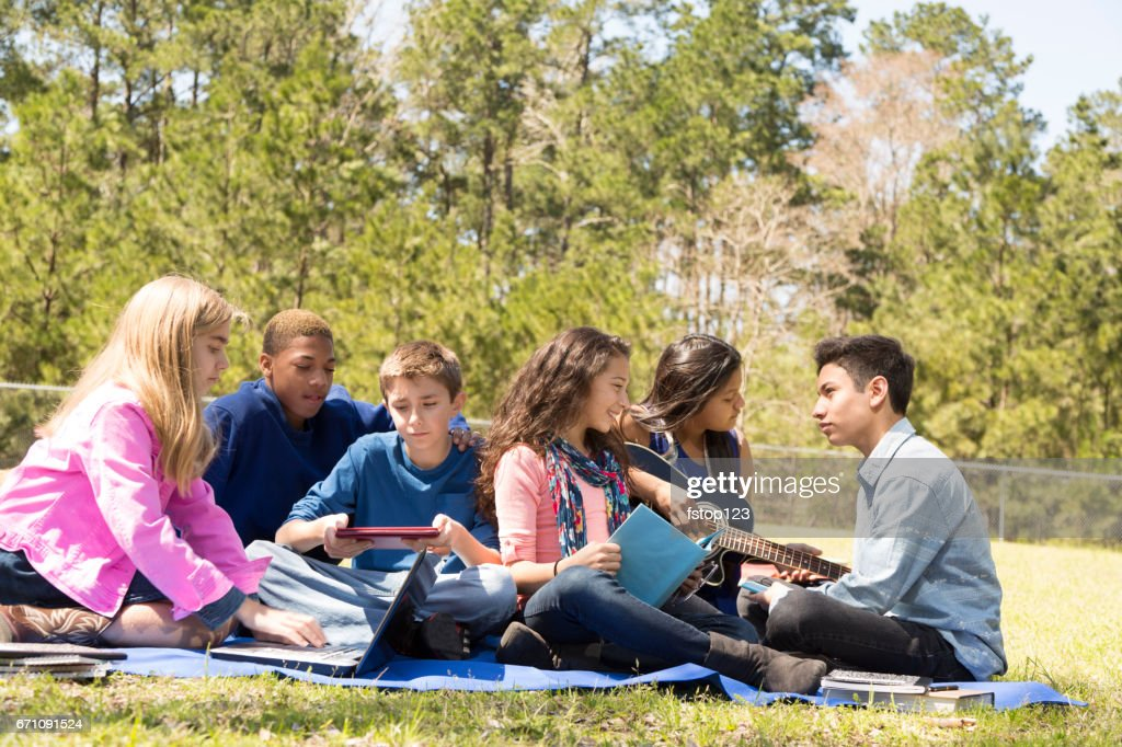 Multi-ethnic group of pre-teenagers hanging out in park with friends. : Stock Photo