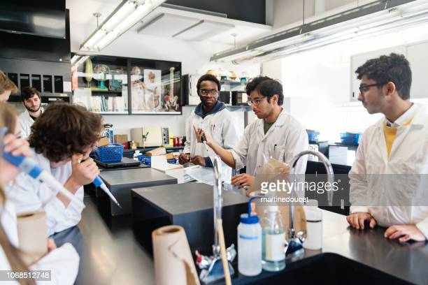 Multi-ethnic group of professors and students in college science laboratory.