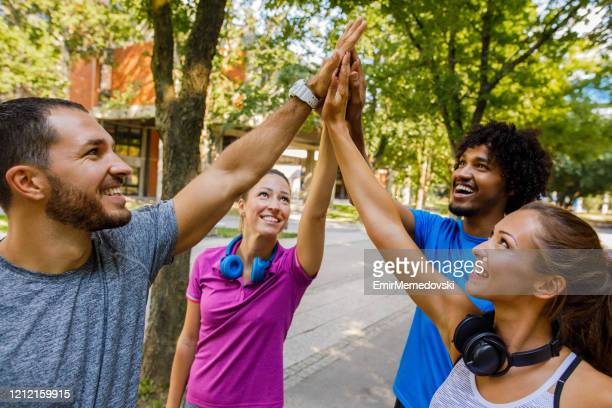 multi-ethnic group of runners high fiving after a good run outdoors - hands clasped stock pictures, royalty-free photos & images