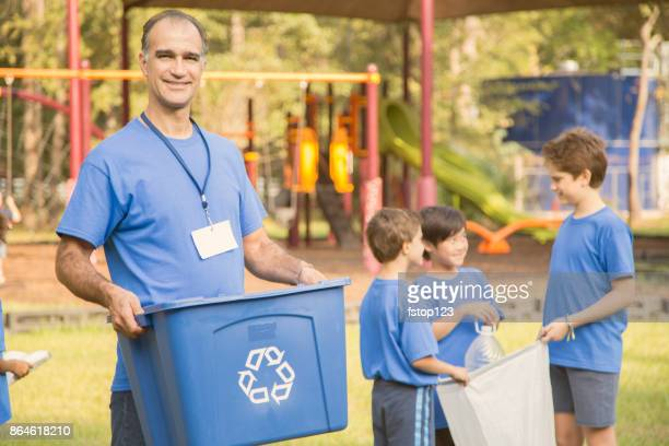 Multi-ethnic group of school children, coach recycling at park.