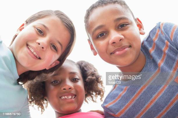 multi-ethnic group of school children friends in huddle. - junior high student stock pictures, royalty-free photos & images