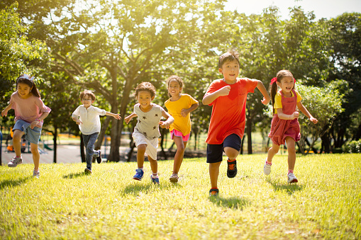 Multi-ethnic group of school children laughing and running 1163705459