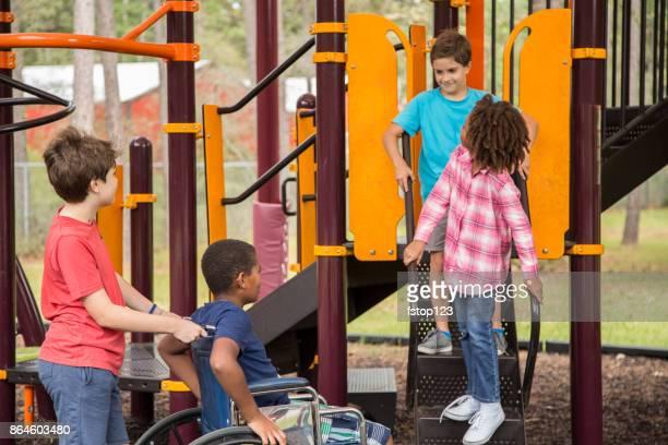 Grupo multiétnico de los escolares en el patio de la escuela, una silla de ruedas.