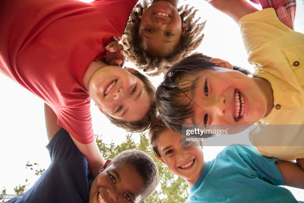 Multi-ethnic group of school children playing on school playground. : Stock Photo
