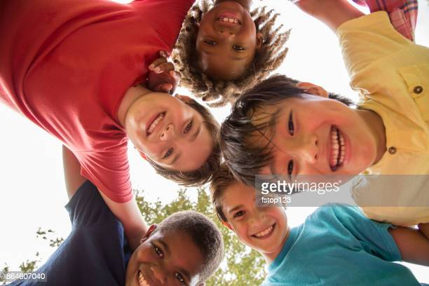 multi-ethnic group of school children playing on school playground. - etnia foto e immagini stock