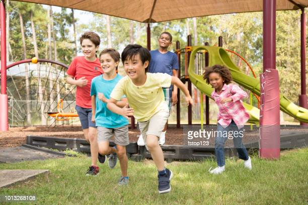Multi-ethnic group of school children running on school playground.