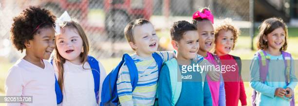multi-ethnic group of school children standing in a row - preschool student stock pictures, royalty-free photos & images