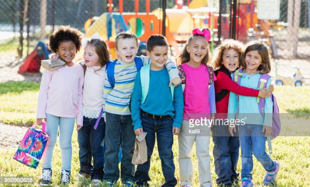 grupo multiétnico de crianças em idade escolar em pé em uma linha - criança de escola fundamental - fotografias e filmes do acervo