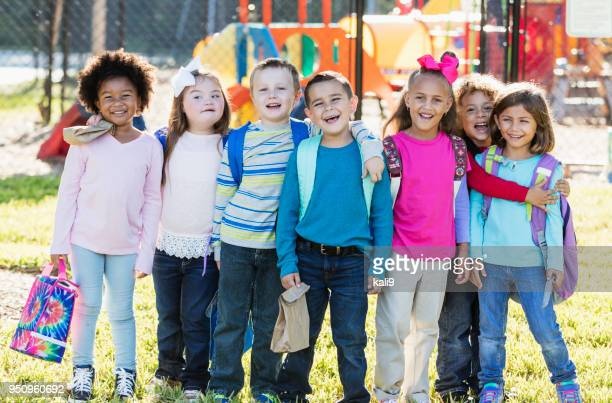 Multi-ethnic group of school children standing in a row