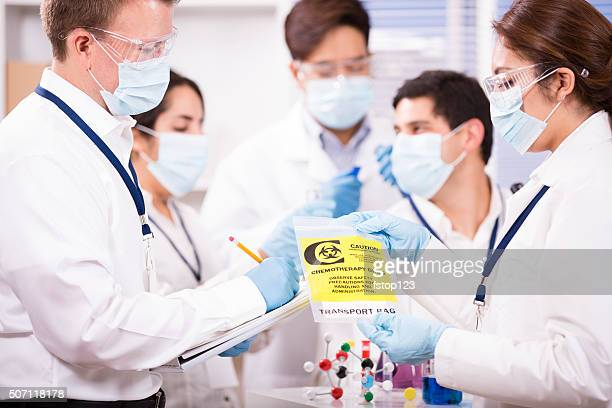 Multi-ethnic group of scientists in science laboratory. Cancer research.