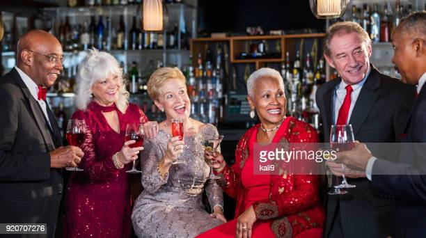 multi-ethnic group of seniors enjoying night out - formalwear stock photos and pictures