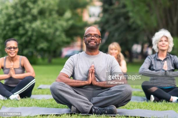multietnisk grupp av seniorer mediterar utomhus - public park bildbanksfoton och bilder