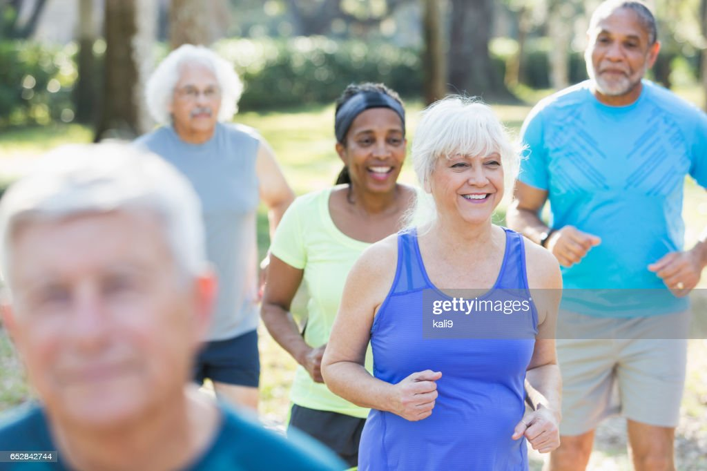 Multi-ethnic group of seniors running in park : Stock Photo