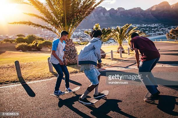Multi-Ethnic Group of Skaters Skateboarding Down Street at Seasi