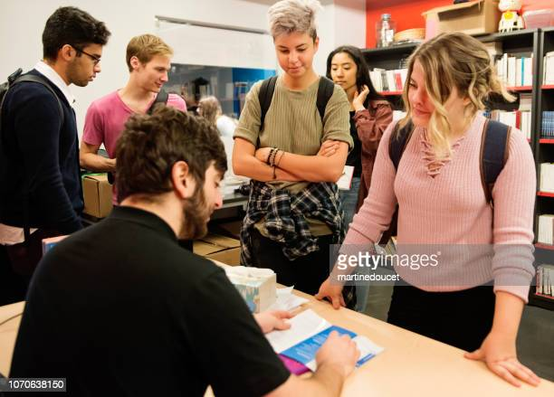 Multi-ethnic group of students buying books in student association classroom.