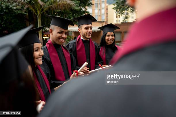 multi-ethnic group of students graduating and looking happy - alumni stock pictures, royalty-free photos & images