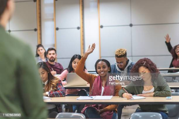 a multi-ethnic group of students listening to presentations - lecture hall stock pictures, royalty-free photos & images
