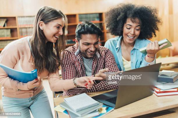 multi-ethnic group of students working together in the library - community college stock pictures, royalty-free photos & images