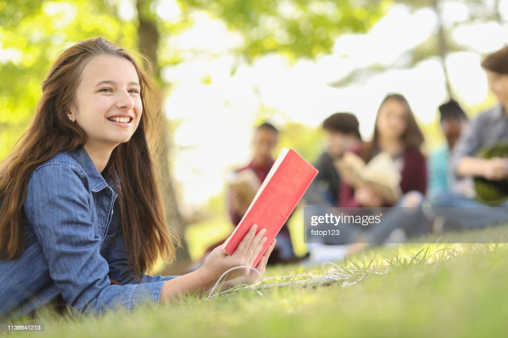 Multi-ethnic group of teenagers at park with friends. : Stock Photo