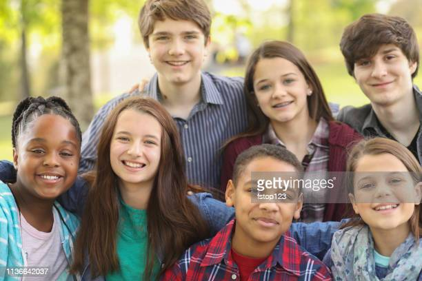 Multi-ethnic group of teenagers at park with friends.