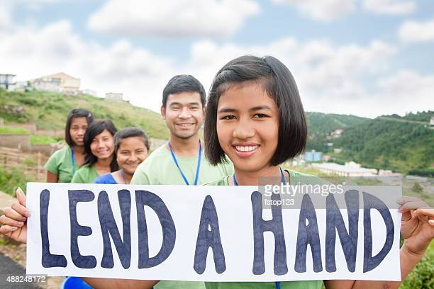 Multi-ethnic group of teenagers hold 'lend a hand' sign outdoors.
